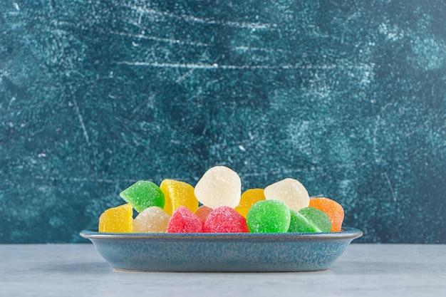 Piatto blu di marmellate di gelatina colorate su marmo.