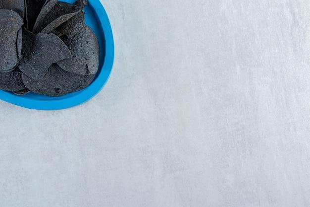 Piatto blu di patatine croccanti nere su pietra.