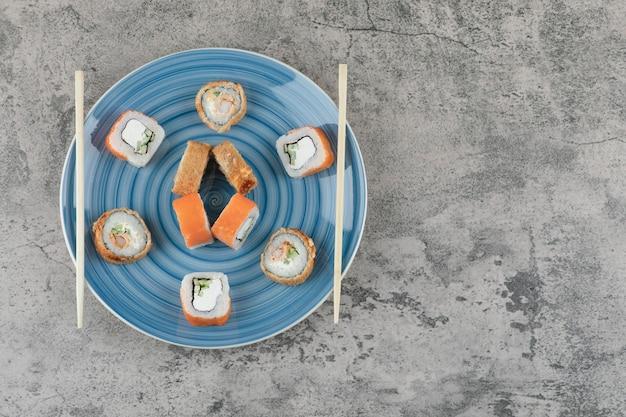Piatto blu di deliziosi involtini di sushi su fondo di marmo