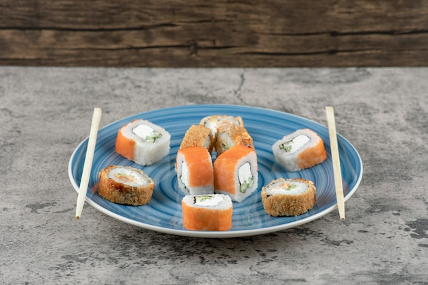 Blue plate of delicious sushi rolls on marble background