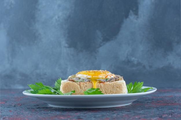 Un piatto blu di deliziosi toast con uovo fritto ed erbe aromatiche