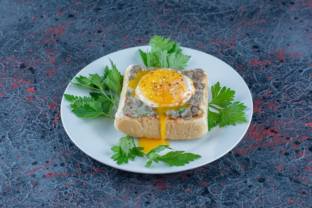 A blue plate of delicious toast with meat and vegetables.