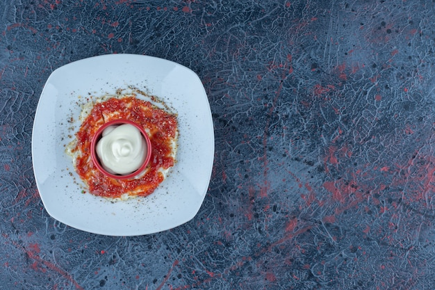 A blue plate of fried egg with spices and tomato sauce.