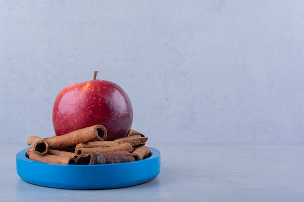 Blue plate full of cinnamon sticks and apple on stone table.