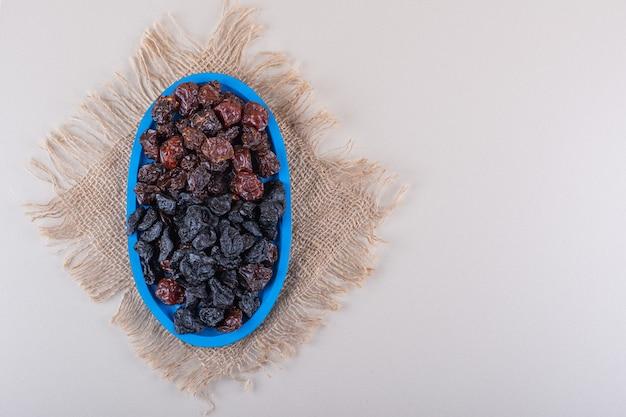 Piatto blu pieno di prugne secche gustose su sfondo bianco. foto di alta qualità