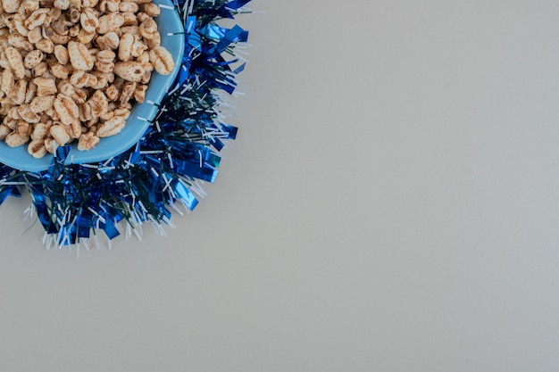 A blue plate full of healthy cereals with a christmas garland .