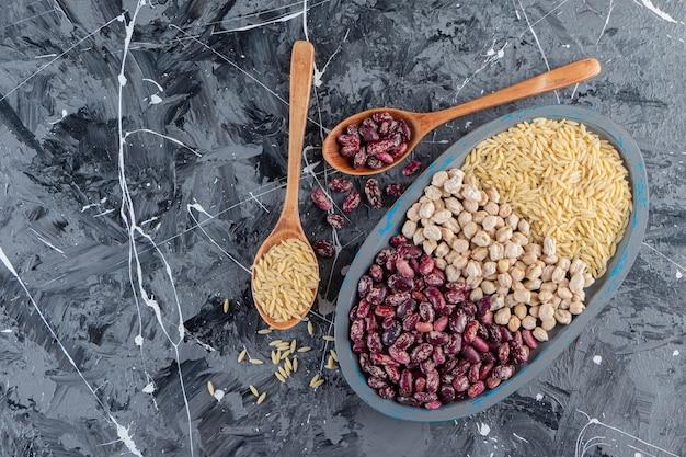 大理石の背景に生のひよこ豆、米、豆でいっぱいの青いプレート。