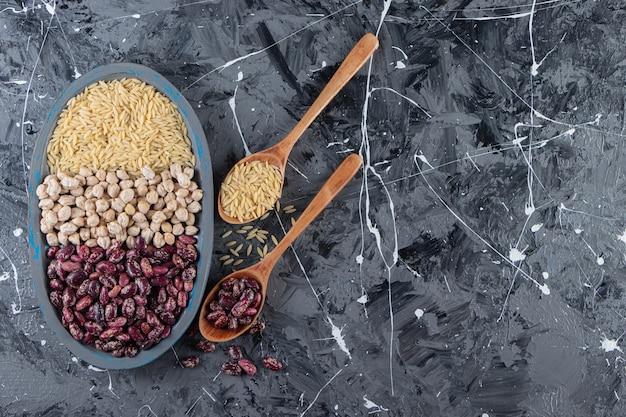 대리석 배경에 생 병아리콩, 쌀, 콩으로 가득 찬 파란색 접시.