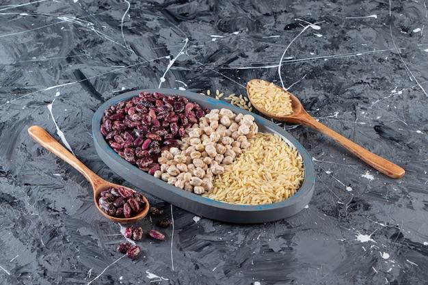 Piatto blu pieno di ceci crudi, riso e fagioli su fondo di marmo.