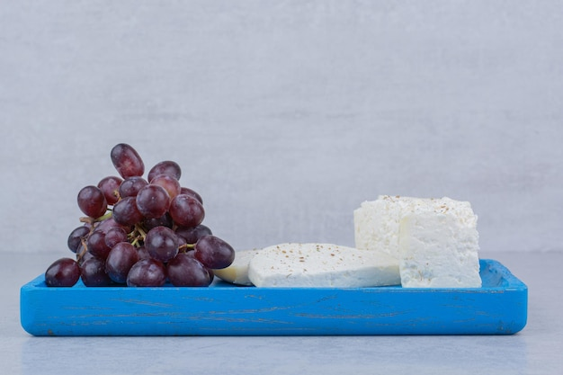 A blue plate full of white cheese and purple grapes . high quality photo