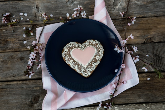 In a blue plate gingerbread heart-shaped and flowering branch of cherry