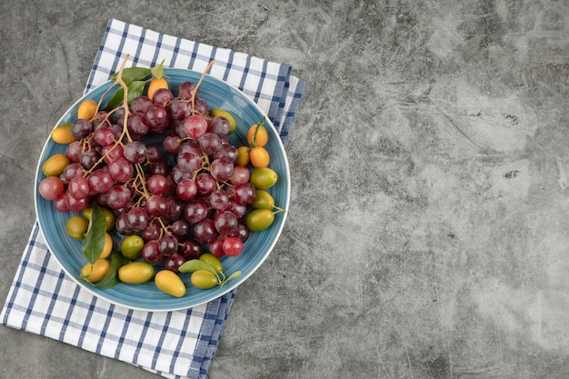 Blue plate of kumquat fruits and red grapes on marble surface.