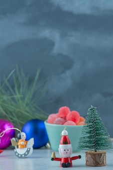 A blue plate of marmalade with small christmas festive toys on marble background. high quality photo