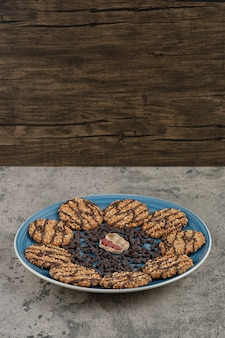비스킷의 파란색 접시, 대리석 배경에 초콜릿과 땅콩을 드롭.