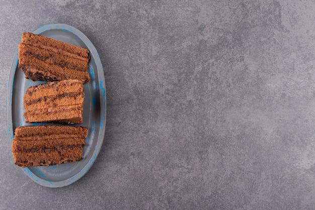초콜릿 케이크의 블루 플레이트는 돌 테이블에 배치합니다.