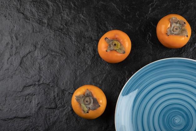 Синяя тарелка вкусной спелой хурмы фую на черной поверхности