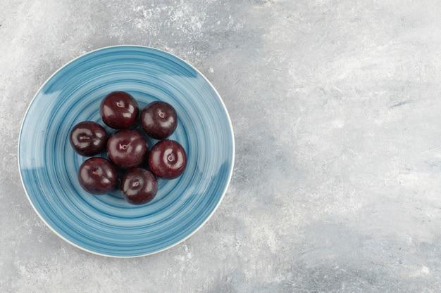 Синяя тарелка свежих фиолетовых слив на мраморной поверхности.