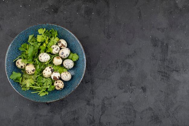 Синяя тарелка свежих сырых перепелиных яиц и листьев петрушки на черном фоне.