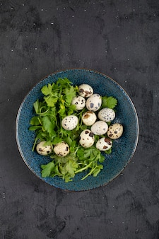 Синяя тарелка свежих сырых перепелиных яиц и листьев петрушки на черной поверхности.