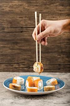 Голубая тарелка филадельфии и горячих суши-роллов на столе.