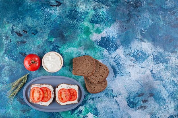 Синяя тарелка тостов со сливками и нарезанными помидорами на мраморной поверхности.