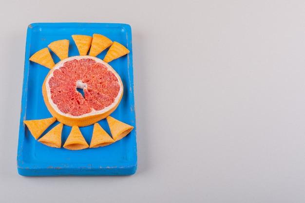 白い背景の上の三角形のチップとグレープフルーツのスライスの青いプレート。高品質の写真