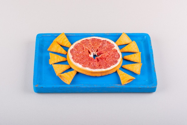 흰색 바탕에 삼각형 칩과 자몽 조각의 파란색 접시. 고품질 사진