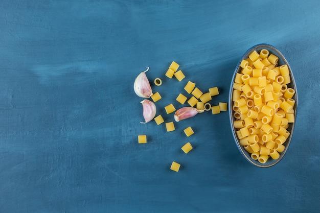 Un piatto blu di pasta cruda ditali rigati con aglio su sfondo blu scuro.