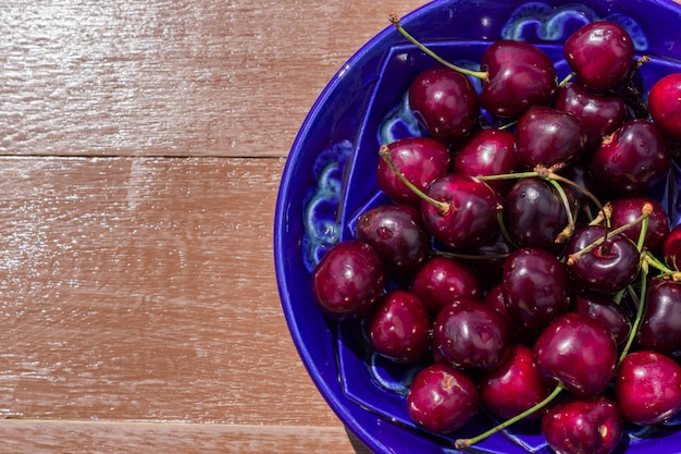 Blue plate of ripe sweet cherry on  wooden table
