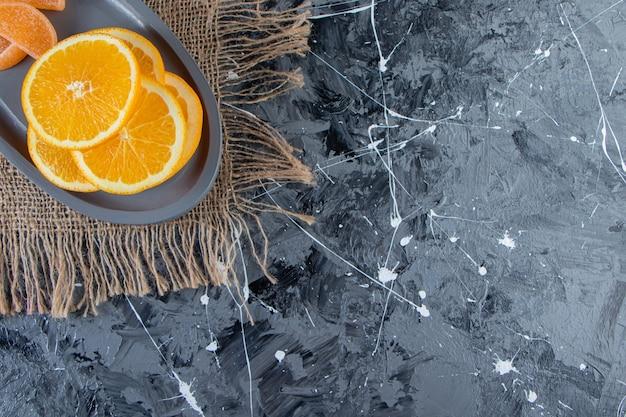 Piatto blu delle arance succose affettate e delle marmellate dolci su tela da imballaggio.
