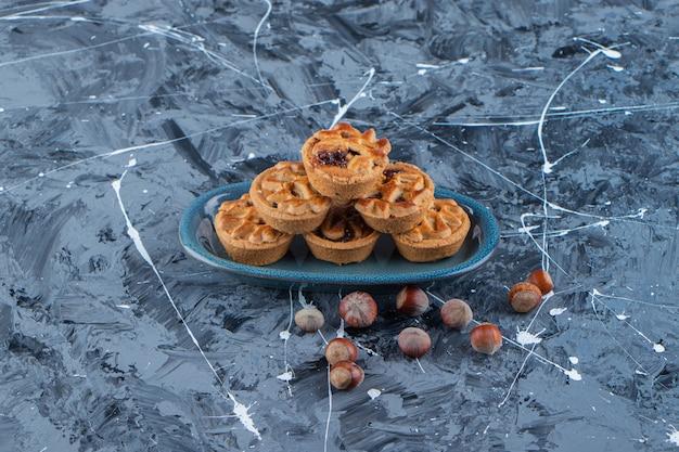 Un piatto blu di tartellette dolci con noci di macadamia su una superficie di marmo.