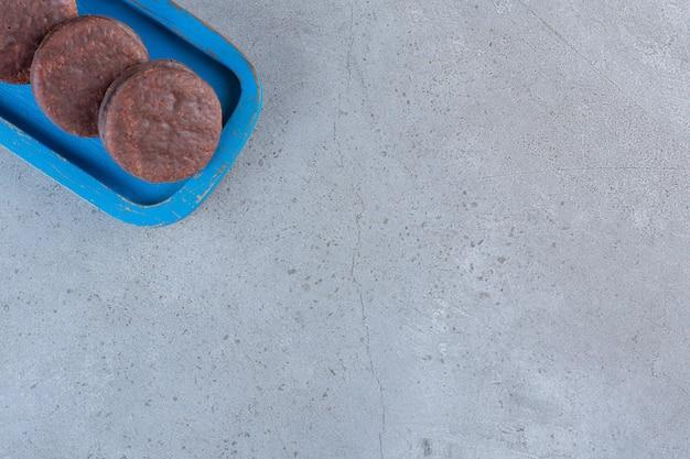 Piatto blu di gustosi biscotti al cioccolato sul tavolo di pietra.
