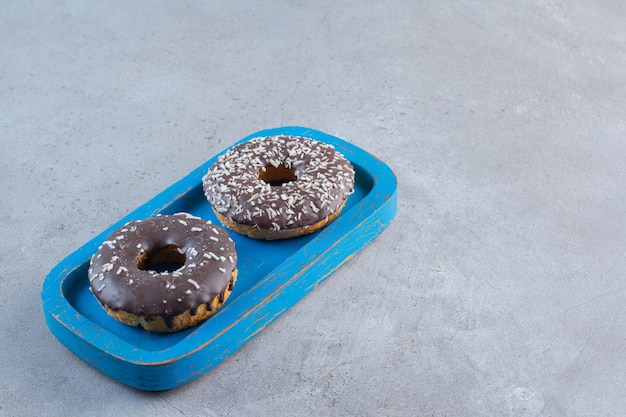 Blue plate of tasty chocolate donuts on stone.