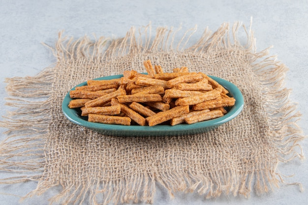 Blue plate of tasty crunchy crackers on stone background.