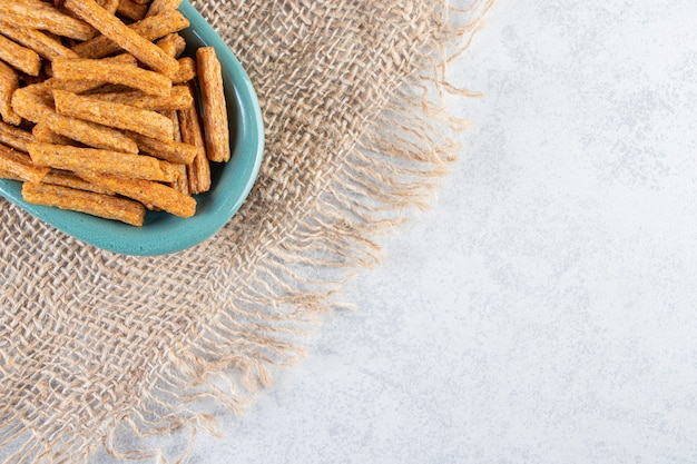 Piatto blu di gustosi cracker croccanti su pietra.