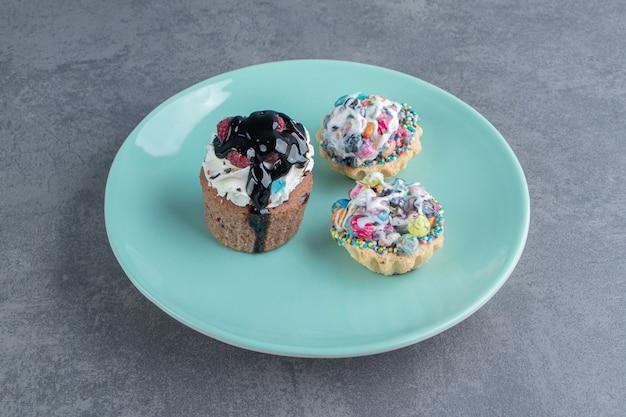 Un piatto blu di tre cupcakes dolci con spruzza