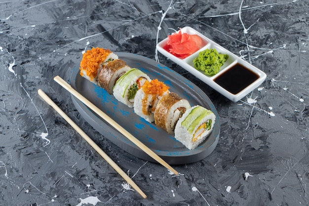 Blue plate of various sushi rolls on marble background.