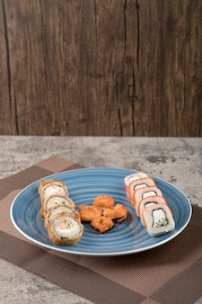 Blue plate of various sushi rolls on marble table