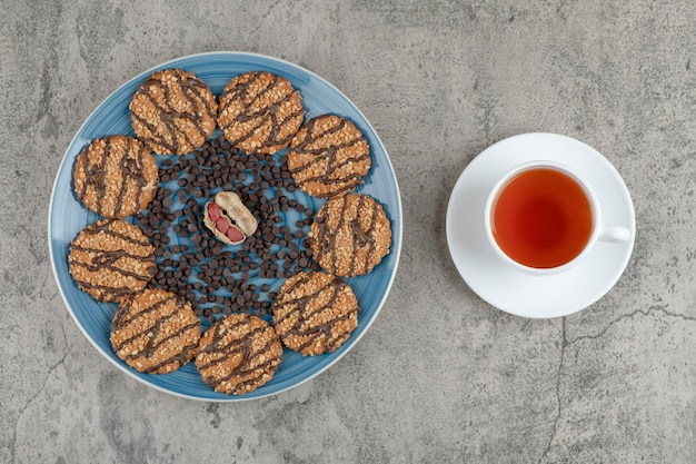 Blue plate with biscuits with chocolate and cup of herbal tea on marble.