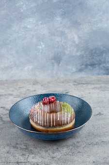 Blue plate with chocolate donut with berry and sprinkles on marble surface.