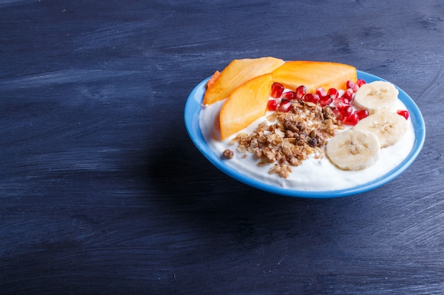 A blue plate with greek yogurt granola persimmon banana pomegranate on black background