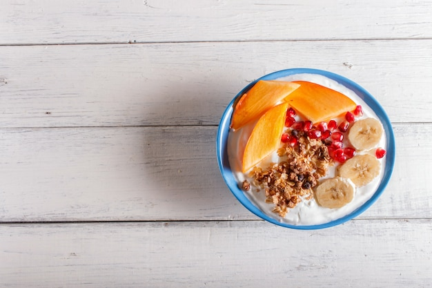 A blue plate with greek yogurt, granola, persimmon, banana, pomegranate on white wooden background.