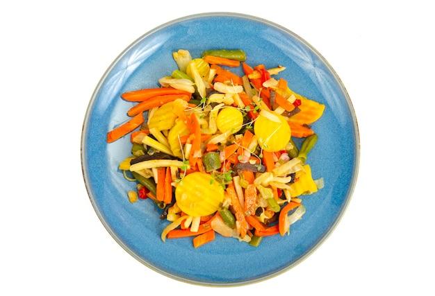 Синяя тарелка с смесью ярких вареных овощей изолированы