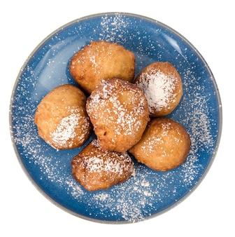 Синяя тарелка с круглыми пончиками с сахарной пудрой, изолированные на белом фоне.