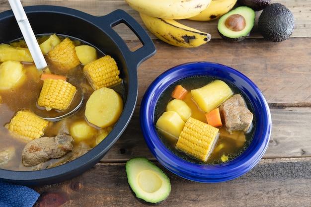 Синяя тарелка с санкочо и горшок на деревянной поверхности. концепция колумбийской кухни.