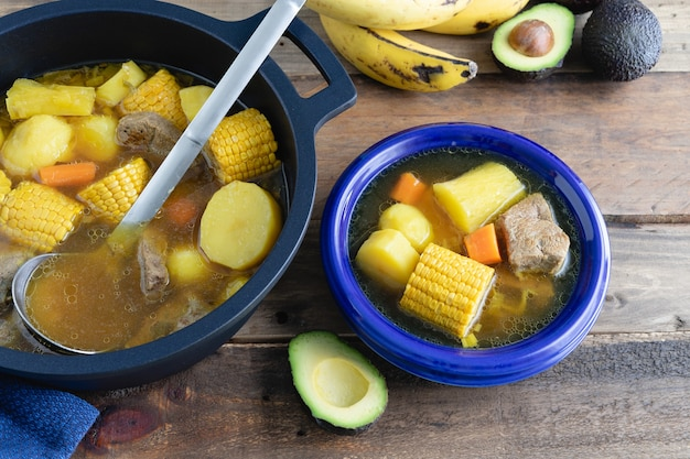 Blue plate with sancocho and pot on wooden background. colombian cuisine concept.