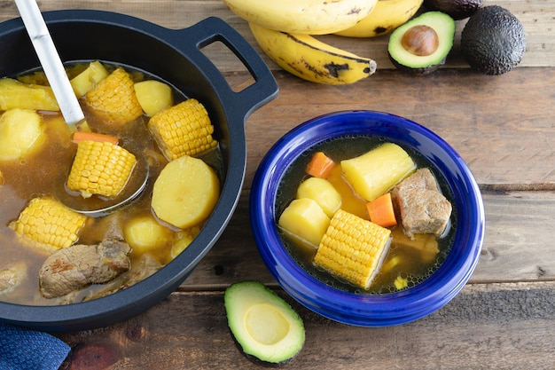 Blue plate with sancocho and pot on wooden surface. colombian cuisine concept. Premium Photo