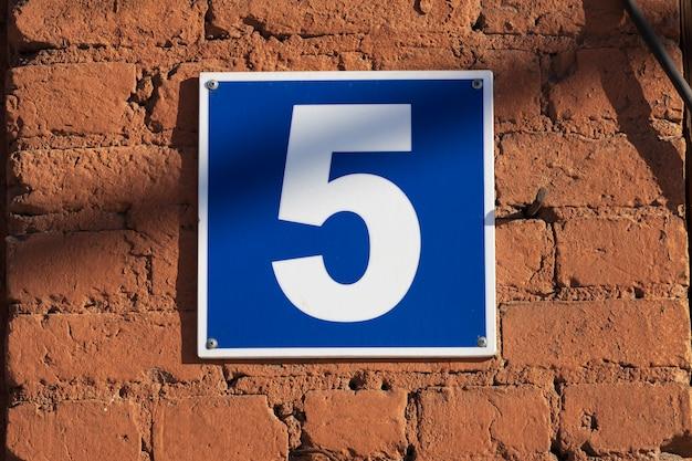 붉은 벽돌 벽에 번호가 있는 파란색 접시