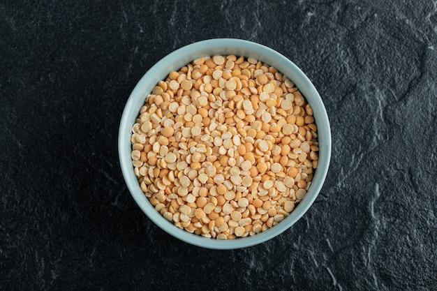 Un piatto blu con popcorn crudo su un fondo scuro