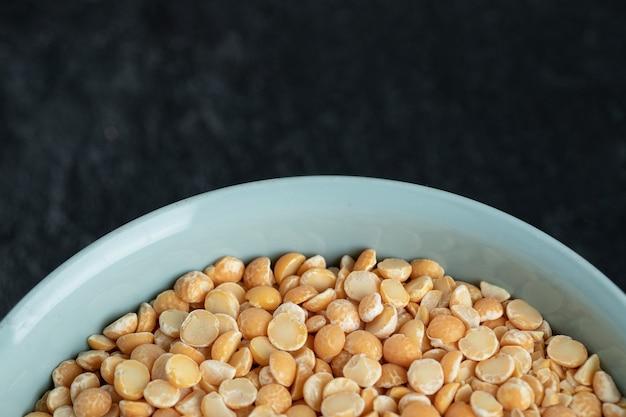 Un piatto blu con lenticchie non preparate al buio